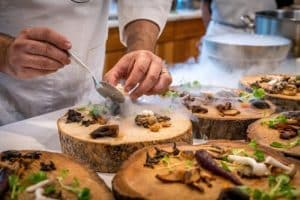 Chef preparing vegetable dish on tree slabs