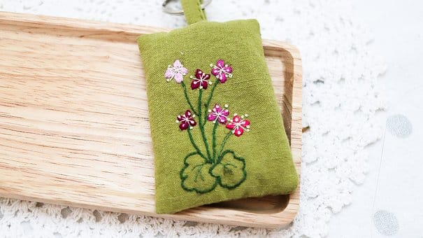 Green embroidered key ring with purple flower pattern