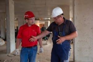 2 workmen wearing hardhats in house under construction