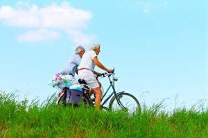 Elderly couple cycling-blue sky-green grass