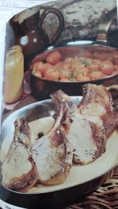 3 pork chops with mustard sauce in a serving dish with caooked carrots in a saucepan