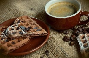 Heart shaped waffles on plate-cup of black coffee-on brown rustic cloth