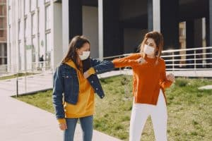 young women in medical masks greeting each other with the elbow